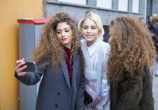 MILAN - 25 FÉVRIER 2018 : Caroline Daur prend un selfie avec deux jumeaux dans la rue avant défilé de mode d'ARMANI, pendant le M Image libre de droits