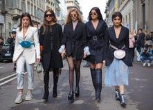 MILAN - 24 FÉVRIER 2018 : Cinq bloggers de mode marchant pour des photographes dans la rue après défilé de mode d'ERMANNO SCERVIN image stock