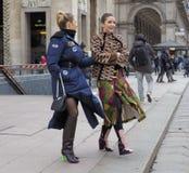 MILAN - 25 FÉVRIER 2018 : Deux femmes à la mode posant pour des photograpers dans la place de Duomo après défilé de mode de STELL Photo stock