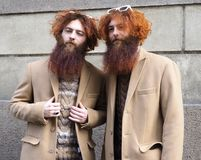 MILAN - FEBRUARY 24, 2018 Two fahionable twins posing for photographers after ERMANNO SCERVINO fashion show. Two fahionable twins posing for photographers after royalty free stock photo