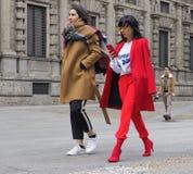 MILAN - FEBRUARY 25, 2018:Two women walking in SAN FEDELE square before MSGM fashion show, during Milan Fashion Week Woman f stock photo