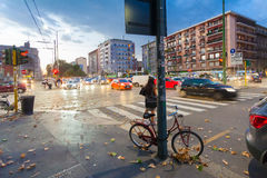MILAN, ITALIE - 6 septembre 2016 : Le rouge a coloré la bicyclette garée attachée par la serrure au poteau de rue dans Milana Image stock