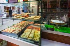 MILAN ITALIEN - September 12, 2016: Smakliga stycken av pizza och läcker focaccia i gatapizzerian Fotografering för Bildbyråer