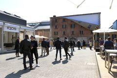Opificio 31 in Tortona district, entrance. In background installation of Alex Chinneck  during Milan Design Week 2019. Milan, Italy - April 9, 2019. Crowd of stock photo