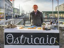 Fresh oysters for sale in Darsena district of Milan, Italy. Ostriciao is Italian for oysters. Friendly salesman,50-55, looks proud. Milan, Italy - Feb 24, 2018 Stock Image