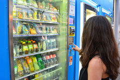 MILAN, ITALY - JULY 19, 2017: Unidentified young student or female tourist choosing a snack or drink at vending machine at night i stock photography