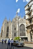 Duomo of Milan and a moving old Mercedes-Benz car. royalty free stock photography