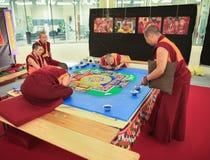 MILAN, ITALY - JUNE 8, 2016: buddhist monks creating mandala fro