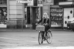 Milan, Italy - March 23, 2016:  Fashion dressed female rides the. Bike on the italian street  in Milan, Italy Royalty Free Stock Photography
