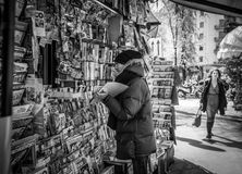 Milan, Italy - March 23, 2016:  Man shows something to newspaper. Seller in Milan, Italy Royalty Free Stock Photo