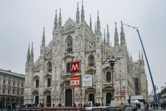 Gothic facade of Milan Cathedral in Piazza del Duomo with lamps and metro sign and M1 line entrance. Milan, Italy - March 1st, 2018: Gothic facade of Milan Stock Photography