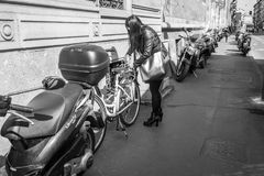 Milan, Italy - March 23, 2016: Young female locking her bicycle. In Milan, Italy Royalty Free Stock Photography