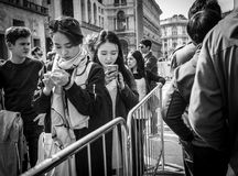 Milan, Italy - March 23, 2016: Young females chatting by phone. Standing in queue in Milan, Italy stock photo