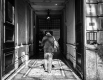 Milan, Italy - March 23, 2016: Young man goes to narrow italian royalty free stock photography