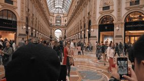 Milan, Italy - May 2019: Asian tourists take pictures in the center of Vittorio Emanuele gallery. The concept of. Shopping and expensive luxury stores. Slow stock video footage