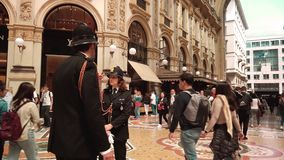 Milan, Italy - May 2019: A female policeman in uniform is patrolling with a male multi-racial policeman in the Vittorio. Emanuele gallery. Concept woman in stock footage