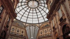 Milan, Italy - May 2019: Glass dome and interior gallery Vittorio Emanuele. The concept of shopping and expensive luxury. Stores. Slow motion, dolly shot stock video footage