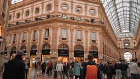 Milan, Italy - May 2019: Large number of tourists and the interior gallery Vittorio Emanuele. Signs of boutiques. Concept of shopping and expensive luxury stock video
