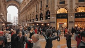 Milan, Italy - May 2019: Many multi-racial tourists and expensive luxury shops in the Vittorio Emanuele gallery. Slow. Motion stock video