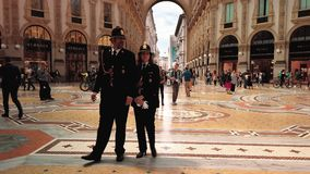 Milan, Italy - May 2019: Two policemen, a man and a woman patrolling in the gallery Vittorio Emanuele. Concept woman in. The male profession. Slow motion stock video
