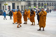 Milan, Italy, 24 nov 2017. Buddhist monks with phones in the square near the Cathedral of Milan royalty free stock image