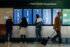MILAN, ITALY - OCTOBER 9, 2017: Airport, people go to the flight departure boards in background. MILAN, ITALY - OCTOBER 9, 2017: Airport, people go to the flight Royalty Free Stock Photos