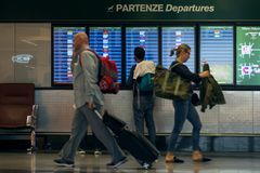 MILAN, ITALY - OCTOBER 9, 2017: Airport, people go to the flight departure boards in background. MILAN, ITALY - OCTOBER 9, 2017: Airport, people go to the flight Stock Photography
