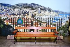 Brown wooden bench and a large panoramic city photo at the Monaco pavilion of the EXPO Milano 2015. royalty free stock photos