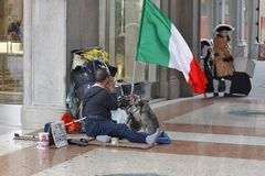 Milan, Italy - One Italian patriot begs for help. MILAN, ITALY - OCTOBER 03: One Italian patriot with a dog begs for help nearby of squere Piazza del Duomo in Royalty Free Stock Image