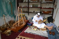 Artisan from Qatar in traditional clothes creating handmade wooden model of ships royalty free stock image