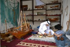 Artisan from Qatar in traditional clothes creating handmade wooden model of ships stock photos