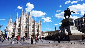 MILAN, ITALY - SEPTEMBER 12, 2017: Piazza del Duomo square with tourists sunny day with sky blue e white clouds, Milan, Italy Royalty Free Stock Photos