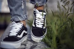 Vans Old Skool shoes in action. Milan, Italy - September 28, 2017: Vans Old Skool shoes in the street - illustrative editorial Stock Photo
