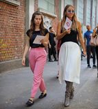 MILAN, Italy, 20 septembre 2018: Women posing for photographers in the street before FENDI stock photography