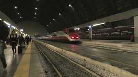 Milan, Italy Trenitalia train Frecciarossa departing. Passengers with luggage walk by Red High Speed Electric Train Frecciarossa departing from Milan Central stock footage