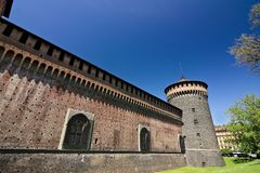 Sforza Castle in Milan. Cylindrical tower and walls. The Castle with the walls and the background of the blue sky of a spring day royalty free stock photo