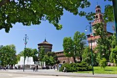 Sforza Castle in Milan. The red brick walls and the tower. Many people walk near the Castle. In the foreground the fountain and stock image