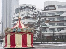 Snowing in Citylife, Milan. Milan, Lombardy, Italy: snow in late winter March at Citylife, the park with residential buildings, the Isozaki tower and a carousel Royalty Free Stock Images