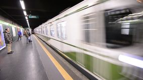 The metro arrives at the stop. Milan, Lombardy region, Italy 30 December at 23:00. The metro arrives at the stop, the passengers approach the yellow line to get stock footage