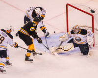 Milan Lucic tries to get the puck past Ryan Miller. Stock Images