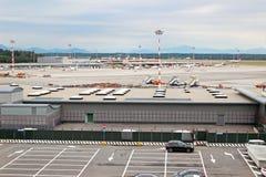 Milan Malpensa Airport. MALPENSA, MILANO, ITALY - AUGUST 01, 2015: View of Milan Malpensa Airport, mountains and car parking. Cloudy weather Royalty Free Stock Image