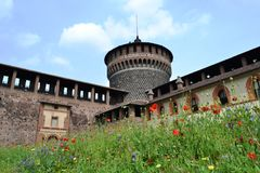 Milan Sforza Castle medieval tower, fortifications, flowering internal garden and ancient brick wall background. Milan Sforza Castle medieval tower and stock image