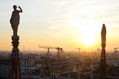 Milan, skyline 2013 at sunset from Duomo cathedral. Milan, end of 2013 new panoramic skyline at sunset. The religious statues of Duomo cathedral faces southwest Royalty Free Stock Photos