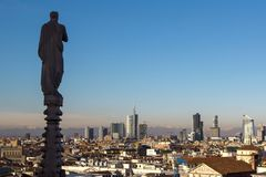 Milan from the top of the gothic cathedral Milan Cathedral, Italy. Church`s roof statues in the foreground, skyscrapers of the ci. Numerous statues on steeples royalty free stock images