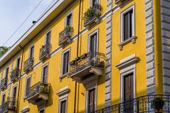 The sun reflects cheerfully on Milanese yellow building in the China Town district. Milanese yellow is often encountered on the historic buildings in Milan Stock Images