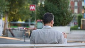 Milano - Businessman reading newspaper on a bench - Cairoli metro subway station on background. Old yellow tram goes into the field stock video footage
