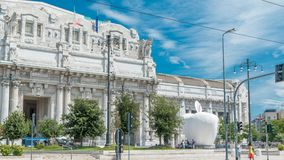 Milano Centrale timelapse in Piazza Duca d`Aosta is the main railway station of the city of Milan in Italy. Apple sculpture. Blue cloudy sky at summer day stock video footage