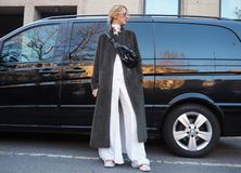 MILANO - 13 gennaio: Una donna alla moda che posa per i fotografi nella via prima della sfilata di moda di NEIL BARRET, durante i Fotografie Stock Libere da Diritti