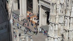 Milano, Italy. The entrance to the famous Vittorio Emanuele shopping mall from the top of the Duomo. The spiers of the Duomo in wh. Ite marble. Spring time stock video footage
