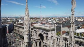 Milano, Italy. The entrance to the famous Vittorio Emanuele shopping mall from the top of the Duomo. The spiers of the Duomo in wh. Ite marble. Spring time stock footage